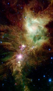Newborn stars, hidden behind thick dust, are revealed in this image of a section of the Christmas Tree Cluster from NASA's Spitzer Space Telescope. The newly revealed infant stars appear as pink and red specks toward the center. | Image: NASA/JPL-Caltech/P.S. Teixeira (Center for Astrophysics)